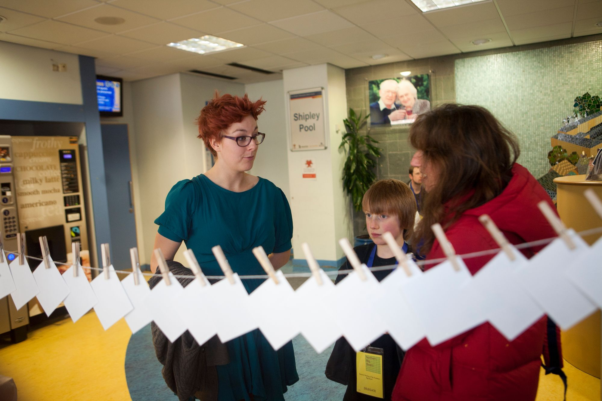 A young woman with red spiky hair and a blue dress on talks to a woman in a red parka in the lobby of a swimming pool, in the front of the shot are a number of cards pegged to a piece of string, they are photographed from the blank side.
