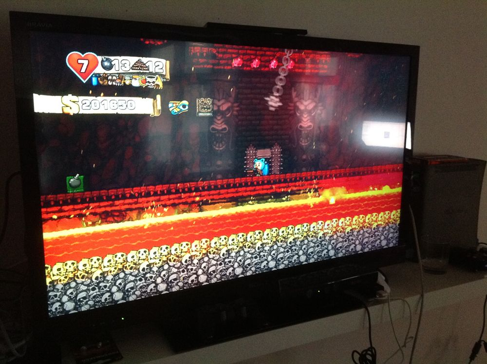 A photo of a tv screen showing the videogame Spelunky. A player character with a shotgun enters Yama's Lair. There's a big bomb box on the left.