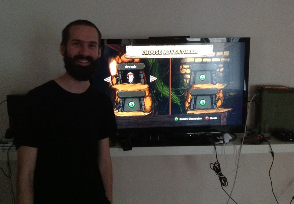 """A photo of Swedish developer Nicklas """"Nifflas"""" Nygren standing in front of a television showing the videogame Spelunky. The screen is on the CHOOSE ADVENTURER screen, with the avatar Yang currently selected."""