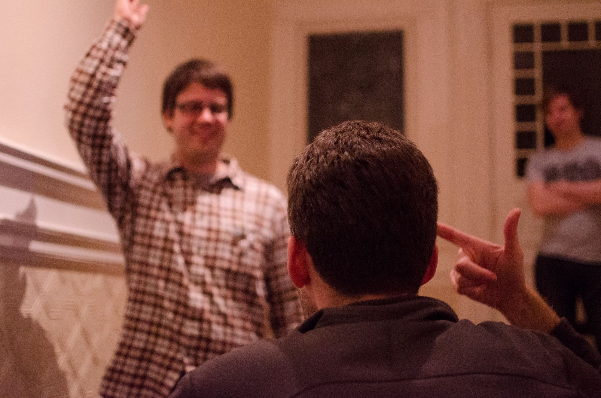 Two men are looking at each other. In the foreground, a man points to his head. In the distance, his opponent is pointing towards the air. The two are playing the folk game Standoff.